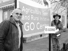 Dave Stead and David Hicks pose next to sign of the provincial farm extension office in Boissevain. They led a protest a week earlier against the move. The office is closing on July 12. Bill Redekop / Winnipeg Free Press