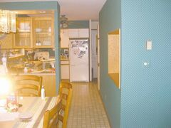 Kitchen before the renovation. The teal-coloured structural wall to the right was knocked down and replaced with a 32-foot overhead laminated beam.