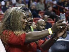 Tennis player Serena Williams, left, poses for a photo with a fan during an NBA basketball game between the Miami Heat and Utah Jazz, Monday, Dec. 16, 2013, in Miami. The Heat defeated the Jazz 117-94. (AP Photo/Lynne Sladky)