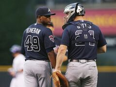 Atlanta Braves starting pitcher Julio Teheran, left, confers with catcher Evan Gattis after Teheran gave up a double to Colorado Rockies' Drew Stubbs in the first inning of a baseball game in Denver on Wednesday, June 11, 2014. (AP Photo/David Zalubowski)
