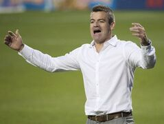 Toronto FC head coach Ryan Nelsen, back argues a call with one of the officials while playing against the Sporting Kansas City during second half MLS soccer action in Toronto on Saturday, July 26, 2014. Toronto FC has fired manager Ryan Nelsen and his entire coaching staff in the wake of Nelsen's public dressing down of general manager Tim Bezbatchenko. THE CANADIAN PRESS/Nathan Denette