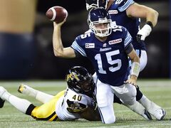 Toronto Argonauts quarterback Ricky Ray, right, tries to get a pass away as he's sacked by Hamilton Tiger-Cats defensive end Eric Norwood during first half CFL action in Toronto on Friday, October 10, 2014. Ray underwent surgery this morning to repair the torn labrum in his right shoulder as well as a small tear in his right rotator cuff. THE CANADIAN PRESS/Frank Gunn