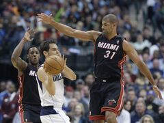 Dallas Mavericks guard Jose Calderon (8) looks to pass against Miami Heat forward Shane Battier (31) and guard Mario Chalmers (15) during the first half of an NBA basketball game Tuesday, Feb. 18, 2014, in Dallas. (AP Photo/LM Otero)