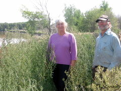 Monica and John Griffiths stand among the weeds growing on top of the dike next to their home.