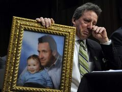 Neil Heslin, the father of a six-year-old boy who was slain in the Sandy Hook massacre in Newtown, Conn., on Dec. 14, holds a picture of himself with his son Jesse and wipes his eye while testifying on Capitol Hill in Washington, Wednesday, before the Senate Judiciary Committee on the Assault Weapons Ban of 2013.
