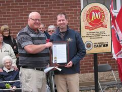 (Left) RM of Cartier reeve Roland Rasmussen receives a proclamation recognizing the municipality's centennial from MLA Shannon Martin (Morris) in Elie on June 14.