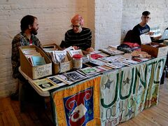 "Musicians Carey J. Buss (left) and Alannah Zeebeck (centre) watch over the Junto zine table. Junto Local 114 is a ""collectively-run lending library which provides rare, radical and relevant political materials"" according to its website"