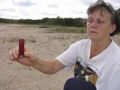 Peggy Kasuba holds up one of thousands of spent shells found in Mars Hills.