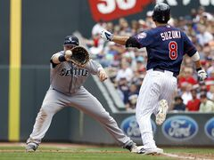 Seattle Mariners first baseman Justin Smoak, left, gets the throw from Mariners starting pitcher Felix Hernandez for the out before Minnesota Twins' Kurt Suzuki (8) can make it to first on a ground ball during the fourth inning of a baseball game in Minneapolis, Sunday, May 18, 2014. (AP Photo/Ann Heisenfelt)
