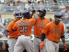 Houston Astros' Jon Singleton (28) is congratulated by teammates George Springer, left, Dexter Fowler and Jonathan Villar, right, after Singleton's grand slam off Minnesota Twins relief pitcher Glen Perkins during the ninth inning of a baseball game in Minneapolis, Sunday, June 8, 2014. The Astros won 14-5. (AP Photo/Ann Heisenfelt)