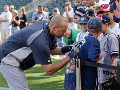 New York Yankees' Derek Jeter autographs a young fans' Jeter shirt prior to the baseball game against the Minnesota Twins, Thursday, July 3, 2014, in Minneapolis. (AP Photo/Jim Mone)