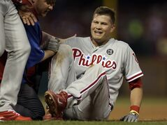 Philadelphia Phillies' Reid Brignac is tended to by a trainer after colliding with St. Louis Cardinals starting pitcher Shelby Miller at first base during the fifth inning of a baseball game on Thursday, June 19, 2014, in St. Louis. Brignac left the game after the collision. (AP Photo/Jeff Roberson)