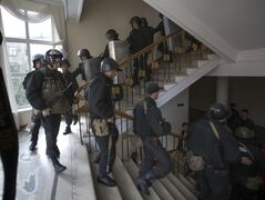 A group of Ukrainian police officers leave the administration building which has been captured by Pro-Russian activists in the center of Luhansk, Ukraine, one of the largest cities in Ukraine's troubled east, Tuesday, April 29, 2014, as demonstrators demand greater autonomy for Ukraine's regions. The Ukrainian police capitulated their position without a fight. The action on Tuesday further raises tensions in the east, where insurgents have seized control of police stations and other government buildings in at least 10 cities and towns.(AP Photo/Alexander Zemlianichenko)