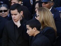 Justin Ramos, the son of slain New York City police officer Rafael Ramos, left, is comforted by his mother, Maritza Ramos, following funeral services at Christ Tabernacle Church, in the Glendale section of Queens, Saturday, Dec. 27, 2014, in New York. Ramos and his partner, officer Wenjian Liu, were killed Dec. 20 as they sat in their patrol car on a Brooklyn street. The shooter, Ismaaiyl Brinsley, later killed himself. Also pictured is officer Ramos' other son, Jaden Ramos, bottom. (AP Photo/Julio Cortez)