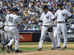 New York Yankees Pitcher Hiroki Kuroda, right, hands the ball to manager Joe Girardi, left, as he leaves the game during the fifth inning of a baseball game against the Cleveland Indians Sunday, Aug. 10, 2014, at Yankee Stadium in New York. (AP Photo/Bill Kostroun)