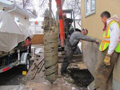 An Abalon Construction crew uses a coring machine to dig below the basement wall so that it can be underpinned. They have removed the soil close to the basement wall leaving room for the boring machine to drill a hole 25 feet below the footing.
