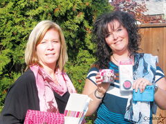 Business owner Kristen Goodman (left) and assistant Shaughn Craig show off some Total She merchandise.