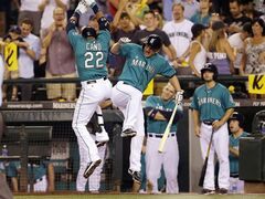 Seattle Mariners' Robinson Cano (22) celebrates with Kyle Seager, center, after Cano hit a solo home run against the Toronto Blue Jays in the sixth inning of a baseball game, Monday, Aug. 11, 2014, in Seattle. (AP Photo/Ted S. Warren)