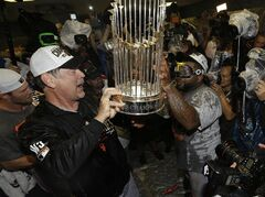 San Francisco Giants manager Bruce Bochy hands the championship trophy to Pablo Sandoval as they celebrate after Game 7 of baseball's World Series against the Kansas City Royals, Wednesday, Oct. 29, 2014, in Kansas City, Mo. The Giants won 3-2 to win the series. (AP Photo/David J. Phillip)