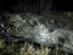 Water starts to flow at a cut made in the embankment near Birdtail Creek near Highway 45.