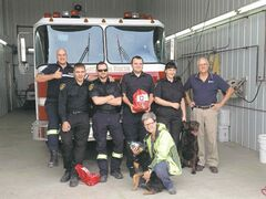 (From left) RM of Cartier firefighters Nathan Lyle, Wesley Butson, Brent Muise, Jonathan Pelchat and Alana Langevin with Fire Services dog Wolf, Invisible Fence Brand of Southern Manitoba co-owner John Dryden, and (in front) Jan Unrau of the St. Francois Xavier Animal Hospital.