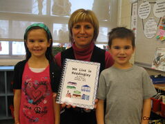 Combined Grade 1 and 2 teacher Melanie Penner with students Olivia and Lake proudly display the book about Headingley that the class created.