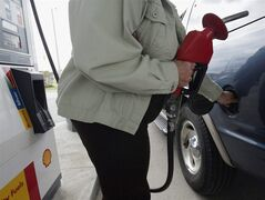 A customer fills her full-size sport-utility vehicle at a Shell station in Mississauga, Ont. in this September 28, 2004 photo. The Sobeys grocery store chain is expanding its gasoline retailing business with the purchase of 250 gas stations in Atlantic Canada and Quebec from Shell Canada. THE CANADIAN PRESS/J.P. Moczulski