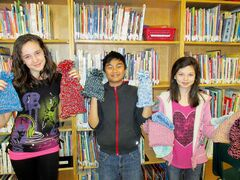 Students show hats they knit for the homeless shelter.