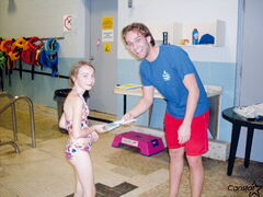 Tyler Belog, instructor/guard at Margaret Grant Pool, hands a course completion certificate to a young swimmer.