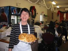 Johnna Yanke shows off the cinnamon buns made at the Little Corner Bakeshop.