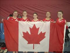 Gabrielle May (second from right) proudly displays the Canadian flag with her teammates after winning the bronze medal in the team event on Tuesday.