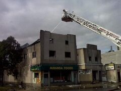 Firefighters work to extinguish a blaze at Miranda Foods on Notre Dame Ave. early Saturday. All residents of the apartments above Miranda Foods were able to get out safely.