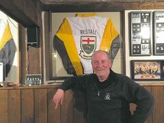 "Howard Restall poses with his 2006 Manitoba Senior Men's Championship, one of many pieces of curling memorabilia he has collected in the ""shrine to the unknown curler"" he maintains in the rec room of his North Kildonan home."