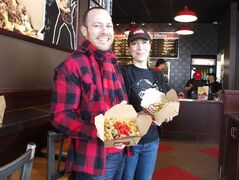 Smoke's Poutinerie founder Ryan Smolkin and local franchisee Cathy Hudson, of Cartier, are shown at the chain's new location at 855 Regent Ave. W. in Winnipeg.