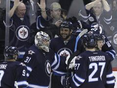 The Jets' Dustin Byfuglien (centre) celebrates his game-winning goal in overtime with his fellow Jets at the end of their 4-3 win over the Carolina Hurricanes.