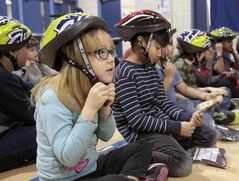 Jolene Clarke,7, and fellow students at Meadows West School received bicycle helmets today at a launch for a new series of bike safety videos and the announcement the low-cost bike helmet initiative will be renewed for another year.