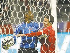 Canada's Will Johnson, right, tries to grab ball from Cuba goalkeeper Odel Molina.
