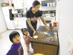 Althea Guiboche, with children Justin and Aralayn, says she's been told she can't bake bannock at home to give to the needy.