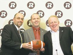 Ottawa Redblacks general manager Marcel Desjardins, left to right, Rick Campbell and owner Jeff Hunt pose for pictures after it was announced Campbell will become the first coach for the new Ottawa Redblacks CFL football tea at a press conference in Ottawa, Friday Dec. 6.