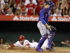 Los Angeles Angels' J.B. Shuck, left, slides into home without the throw getting to Texas Rangers catcher J.P. Arencibia, right, after a base hit by Howie Kendrick to right field in the fourth inning of a baseball game on Friday, May 2, 2014, in Anaheim, Calif. (AP Photo/Alex Gallardo)