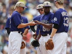Colorado Rockies manager Walt Weiss, front left, takes ball from starting pitcher Yohan Flande, front center, as first baseman Justin Morneau, front right, third baseman Nolan Arenado, back left, and shortstop Troy Tulwitzki, back center, look on against the Los Angeles Dodgers in the fifth inning of a baseball game in Denver, Sunday, July 6, 2014. Flande had just walked Dodgers' Scott Van Slyke to load the bases with one out in the inning. (AP Photo/David Zalubowski)