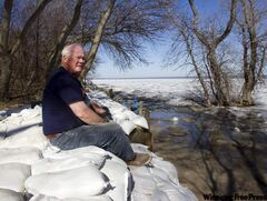Retired school principal Larry Muirhead watches the rising waters of Lake Manitoba from his sandbagged backyard in Delta Beach, Man. on Monday.