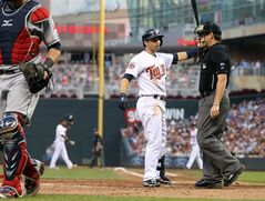 Minnesota Twins' Brian Dozier has some conversation with plate umpire D.J. Reyburn right, after he was called out looking in the fourth inning of a baseball game against the Cleveland Indians, Tuesday, July 22, 2014, in Minneapolis. (AP Photo/Jim Mone)