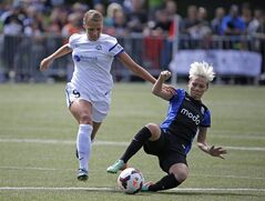 FC Kansas City's Merritt Mathias, left, and Seattle Reign FC's Jessica Fishlock race for the ball in the first half of the NWSL championship soccer match Sunday, Aug. 31, 2014, in Tukwila, Wash. (AP Photo/Elaine Thompson)