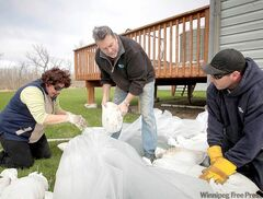 Lynn (from left) and Les Kauppila and Kelly Chabot start work on a sandbag dike around the Kauppilas� home in Elie.