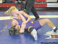 Liz Sera (in purple) puts an opponent on the mat. She's on a scholarship at the University of Western Ontario and winning medals in wrestling competitions.