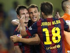 Barcelona's Sandro, center, is congratulated by teammate Lionel Messi, from Argentina, left, after scoring a goal against Villarreal during a Spanish La Liga soccer match at the Madrigal stadium in Villarreal, Spain, on Sunday, Aug 31, 2014.(AP Photo/Alberto Saiz)