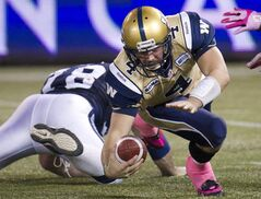 Winnipeg Blue Bombers quarterback Buck Pierce, right, gets sacked by Toronto Argonauts defensive tackle Adriano Belli during first-half CFL  action in Toronto Friday.