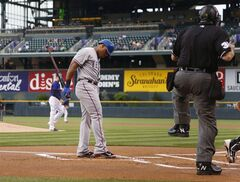 Texas Rangers' Adrian Beltre, left, reacts to called strike three by home plate umpire Gary Cedarstrom to end the top of the first inning against the Colorado Rockies in an interleague baseball game in Denver on Monday, May 5, 2014. (AP Photo/David Zalubowski)