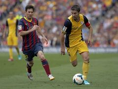 Barcelona's Lionel Messi from Argentina, left, and Atletico's Gabi challenge for the ball during a Spanish La Liga soccer match between FC Barcelona and Atletico Madrid at the Camp Nou stadium in Barcelona, Spain, Saturday, May 17, 2014. (AP Photo/Emilio Morenatti)